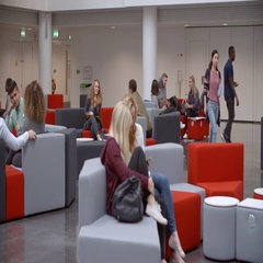 Groups of students socialising in the lobby of a university Stock Footage