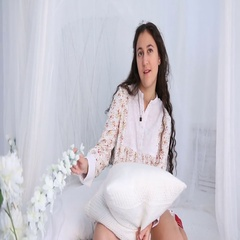 Young girl sitting on a white bed in a dress Stock Footage
