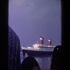 1960: people on the shore watch a cruiseliner get escorted from port  Stock Footage