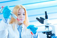 Young woman technician use pipette in laboratory Stock Photos