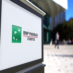 Street signage board with BNP Paribas logo. Blurred office center and walking Stock Footage