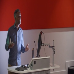 Teacher at lectern and students in lecture theatre, close up Stock Footage
