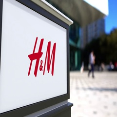 Street signage board with H&M logo. Blurred office center and walking people Stock Footage