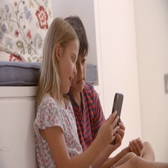 Two Children Sitting On Floor And Playing With Smartphone Stock Footage