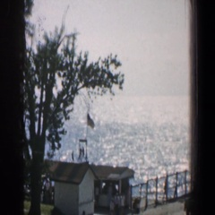 1961: panorama shot of ocean and cars parked on the dock with people walking Stock Footage