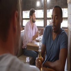 Two male friends in a bar making a toast with beer bottles Stock Footage