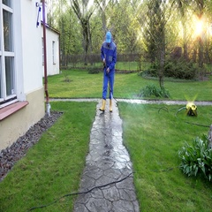 Housekeeper guy washing concrete path near his house Stock Footage