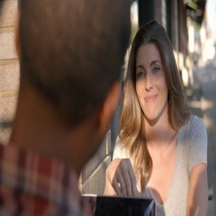 Mixed race couple relaxing at a table outside a coffee shop Stock Footage