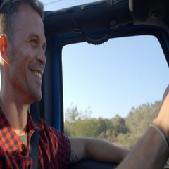 Young man driving in an open top car in Summer, close up Stock Footage