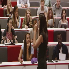 Female teacher talking with students in a lecture theatre, shot on R3D Stock Footage