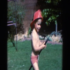 1961: a small boy playing fireman in the backyard NORTH HOLLYWOOD, CALIFORNIA Stock Footage