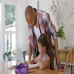 Father Helping Daughter With Homework At Table Stock Footage