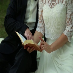 Yong bride and groom sitting in the park and ridding the book Stock Footage