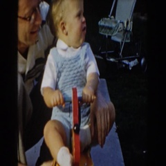 1962: dad and son playing on a rocking puppy toy. GLENDALE, CALIFORNIA Stock Footage