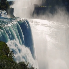 Niagara Falls in the sun. A huge cloud of spray and mist, the ship sails away Stock Footage
