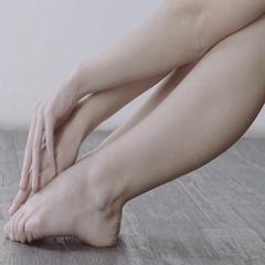 Woman gently touching her legs sitting on wooden floor with white wall on Stock Footage