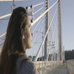 Young Woman Walks Toward Railing Of Bridge, Touches It, Looks Out At View Stock Footage