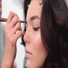 Stylist paints eyebrows, make up artist at work, model preparing for photoshoot Stock Footage