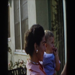 1962: toddler tries to pull earring off mother's ear GLENDALE, CALIFORNIA Stock Footage
