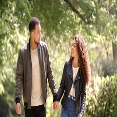Couple holding hands, walking in a rural setting, front view Stock Footage