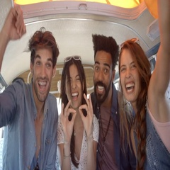 Four excited adult friends on a road trip in a camper van Stock Footage