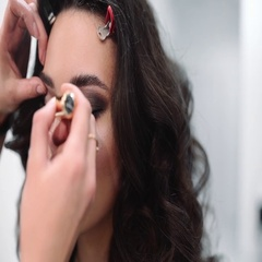 Make up artist paints lashes, beautiful sexy woman at the beauty salon Stock Footage