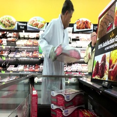 Clerk stocking forzen meat for sale inside Walmart store with 4k resolution Stock Footage