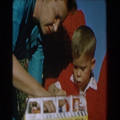 1962: family gathering on a birthday as little boy learns to play with his toys. Stock Footage