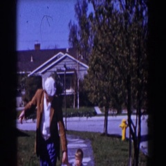 1962: man in white beret and brown jacket walking child across yard GLENDALE Stock Footage