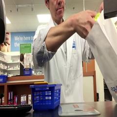 Pharmacist explaining prescription to customer inside Walmart store Stock Footage