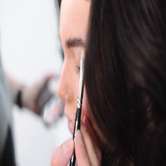 Make up stylist makes smokey eyes effect for woman at photo shoot Stock Footage