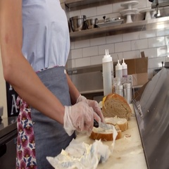 Woman buttering bread at a sandwich bar, mid section Stock Footage