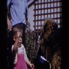 1962: toddler feeding a doggy outside. GLENDALE, CALIFORNIA Stock Footage