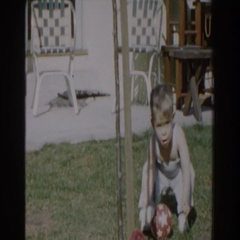 1962: little boy picking up a toy ball out in the yard. GLENDALE, CALIFORNIA Stock Footage