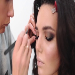 Make up artist making long lashes, woman in beauty studio makes evening make up Stock Footage