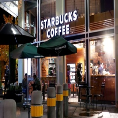 People enjoying coffee inside Starbucks coffee at night Stock Footage