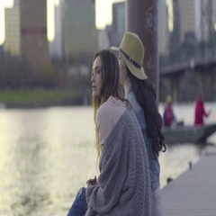 Young Women Sit On A Dock, Look At Sunset Over Water, Boat Pulls Up Behind Them Stock Footage
