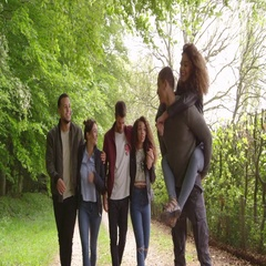 Young adults walking and piggybacking in a country lane, shot on R3D Stock Footage