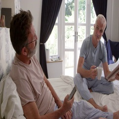 Homosexual Couple Relaxing In Bedroom Reading Newspaper Stock Footage