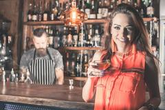 Beautiful girl is drinking a cocktail with ice vapor in the bar Stock Photos