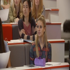Handheld tilt shot of students in university lecture theatre Stock Footage
