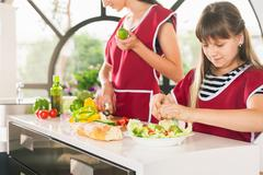 Family of young girls cooking. Recipe healthy food for kids Stock Photos