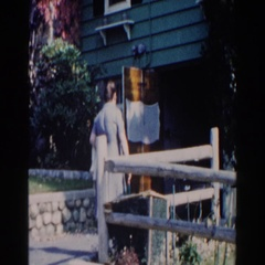 1960: a woman in a dress and pinafore playfully shakes wine bottle at camera Stock Footage