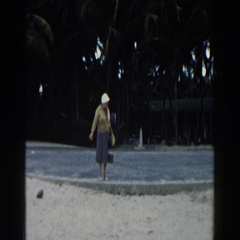 1960: grandmother enjoys beachcombing during family vacation to island paradise. Stock Footage
