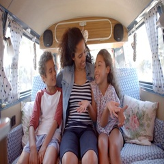 Smiling mum and kids travelling in the back of a camper van Stock Footage