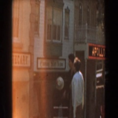 1961: family of three on a slow, casual stroll pass dimly lit display windows Stock Footage