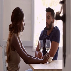 Young adult couple sit drinking wine and talking in kitchen, shot on R3D Stock Footage