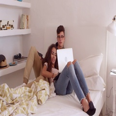 Teenage couple hanging out in bedroom using laptop, shot on R3D Stock Footage
