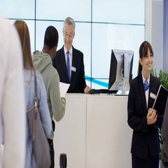 4K Friendly bank worker at service desk assisting customers with enquiries Stock Footage