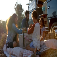 Family eating picnic outside their camper van at sundown Stock Footage